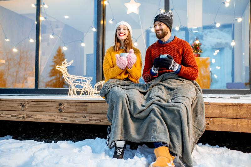 Couple warming up near the house during the winter holidays. Young couple warming up with plaid and hot drinks sitting on the terrace of the modern house in the royalty free stock photos