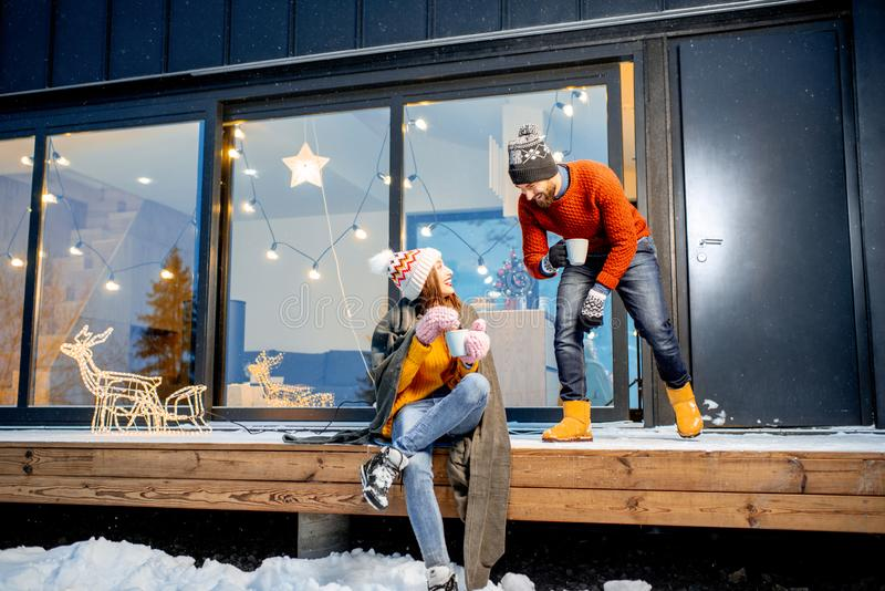 Couple warming up near the house during the winter holidays. Young couple warming up with plaid and hot drinks sitting on the terrace of the modern house in the stock photography