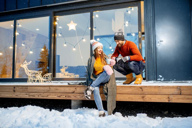 Couple warming up near the house during the winter holidays. Young couple warming up with plaid and hot drinks sitting on the terrace of the modern house in the stock photo
