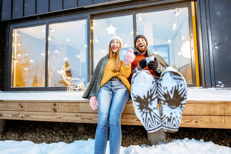 Couple warming up near the house during the winter holidays. Young couple warming up with plaid and hot drinks sitting on the terrace of the modern house in the royalty free stock photo