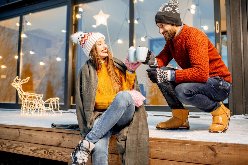 Couple warming up near the house during the winter holidays. Young couple warming up with plaid and hot drinks sitting on the terrace of the modern house in the royalty free stock photography