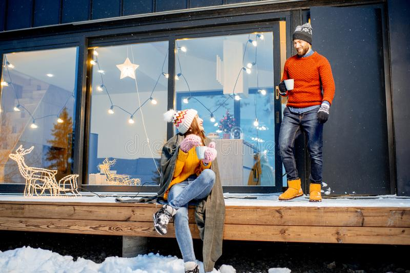 Couple warming up near the house during the winter holidays. Young couple warming up with plaid and hot drinks sitting on the terrace of the modern house in the royalty free stock images