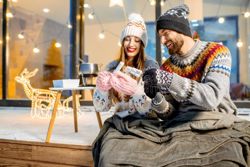Couple warming up near the house during the winter holidays. Young couple warming up with plaid and marshmallow sitting on the terrace of the modern house in the royalty free stock image