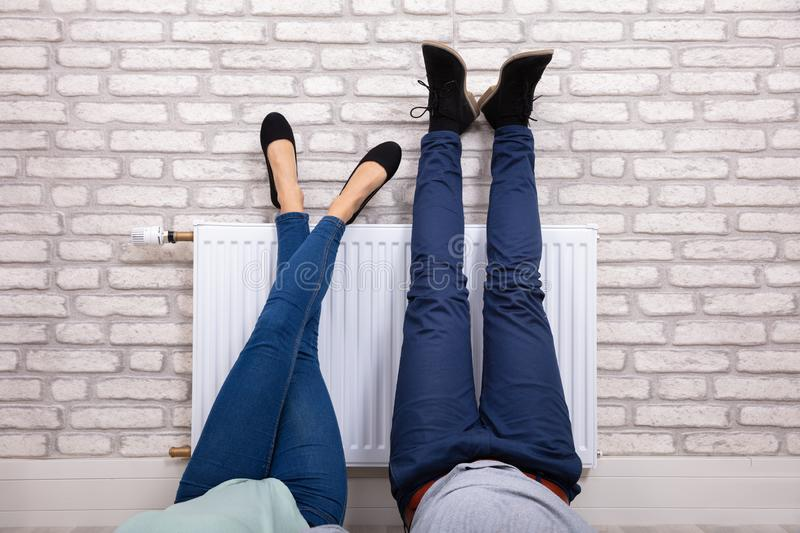 Couple Warming Up Their Feet On Radiator stock photo