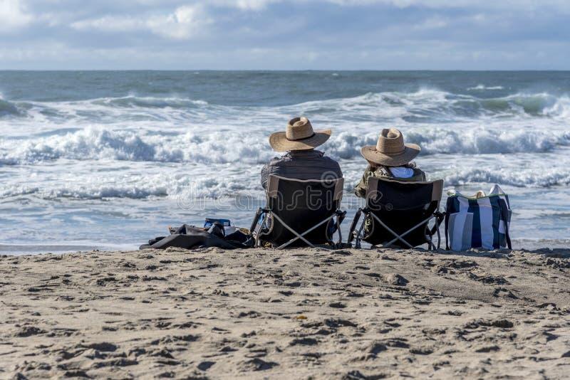 A couple watch the sea at Santa Cruz Natural Bridges state beach. Santa Cruz, California, USA January 13 2019. The beach at Natural Bridges State Beach with sand royalty free stock images