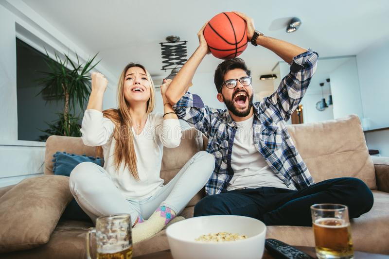 Couple is watching basketball game. On the sofa at home stock images
