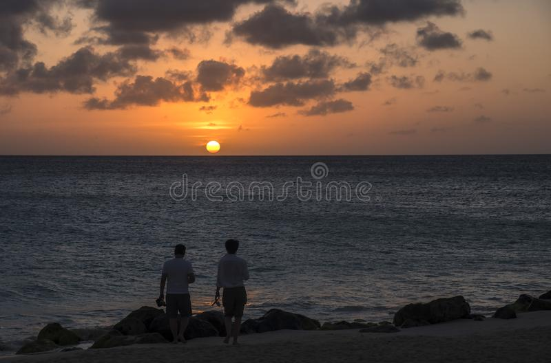 A Couple Watching BeautifulSunset Over the Caribbean Sea 1 royalty free stock photos
