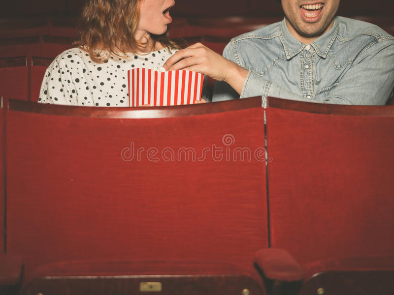 Couple watching a film in a movie theater. A young couple is watching a film in a movie theater and the men is stealing the woman's popcorn to her dismay royalty free stock photo
