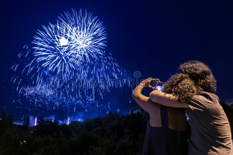 Couple watching fireworks show. Couple in love man and woman are hugging and watching fireworks show