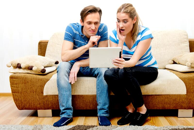 Couple watching movie on tablet. Couple sitting on sofa and watching movie on tablet. Streaming media on internet stock photo