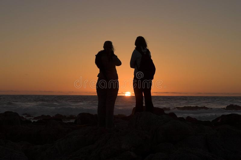 Couple watching ocean sunset. Rear view of silhouetted couple watching colorful ocean sunset stock photos