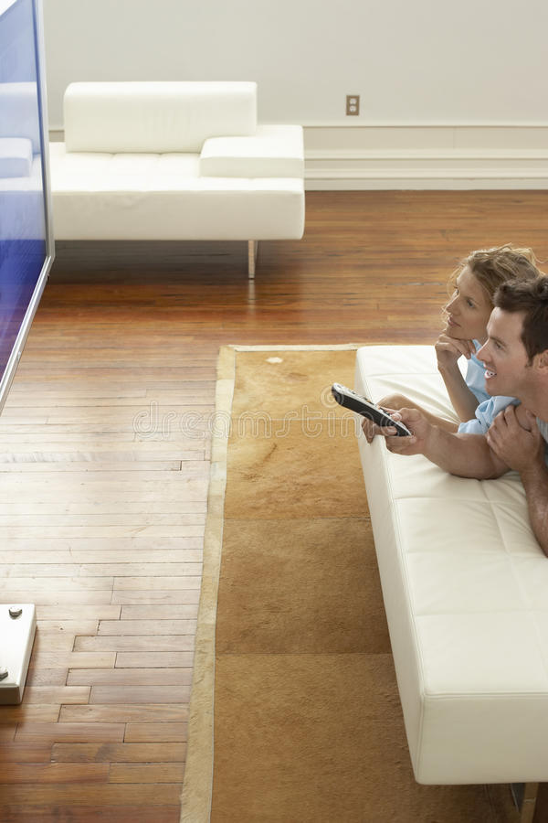 Couple Watching Plasma TV At Home. Happy young couple watching plasma TV in modern apartment royalty free stock photos