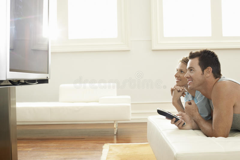 Couple Watching Plasma TV At Home royalty free stock images