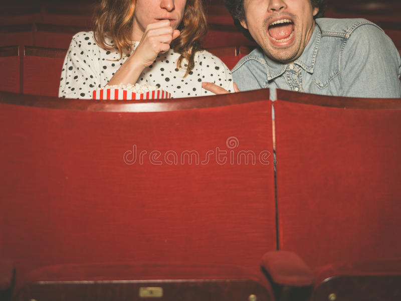 Couple watching a scary film in a movie theater. A young couple is watching a scary film in a movie theater stock image