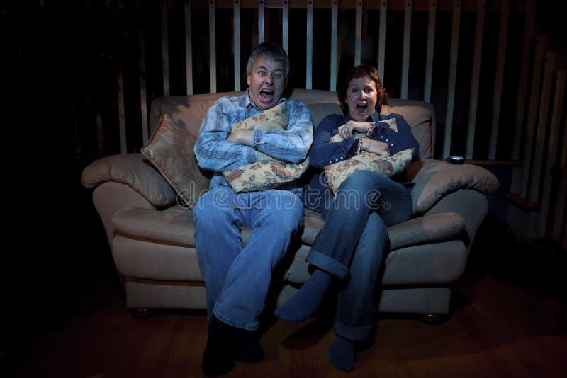 Couple watching scary movie stock photos