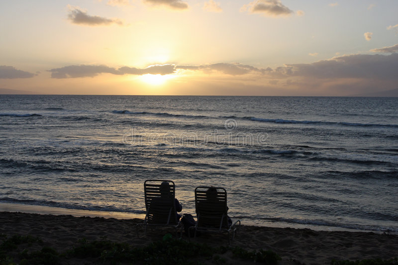 Couple Watching the Sunset. A couple watching the sun set over the Pacific ocean in Maui royalty free stock photo