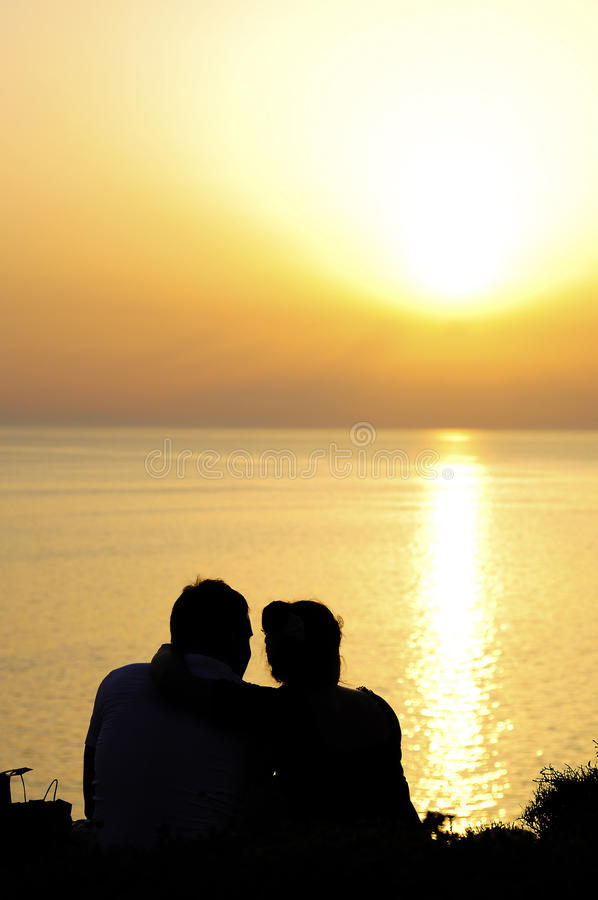 Couple watching the sunset in beach stock photos