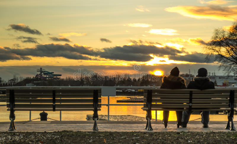 Couple watching the sunset. Lovers looking at the sunset sitting on a bench royalty free stock photo