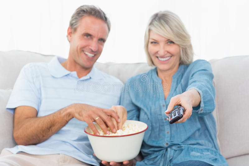 Download Couple Watching Tv And Eating Popcorn On The Couch Stock Photo - Image: 32513402