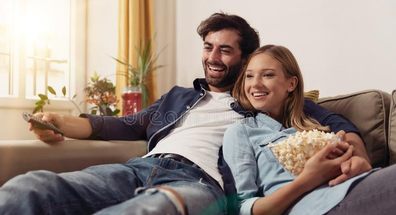 Couple watching TV on a sofa at home. Couple watching TV, eating popcorn on a sofa at home royalty free stock images