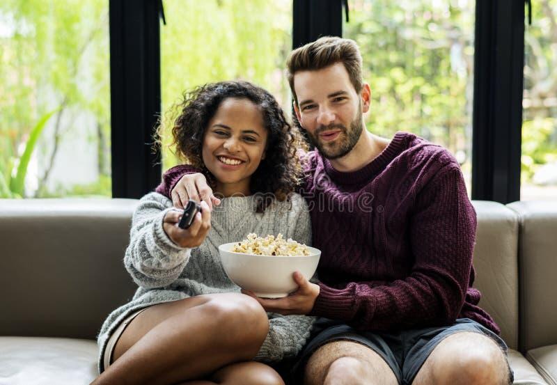 Couple watching TV having popcorn stock images