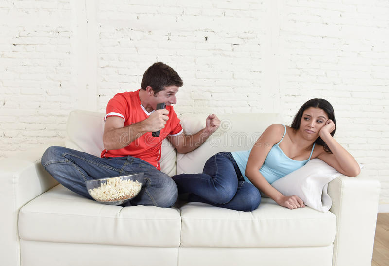 Couple watching tv sport football with man excited celebrating royalty free stock photography