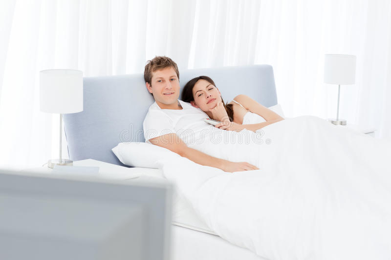 Download Couple Watching Tv In Their Bed Stock Photo - Image of lifestyle, intimacy: 17937072