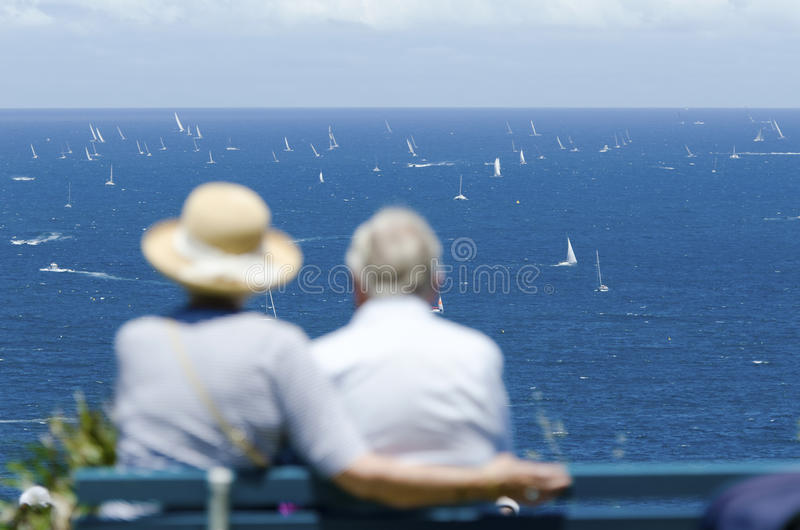 Couple watching yacht race. An old couple sitting on the bench and watching a yacht race stock image