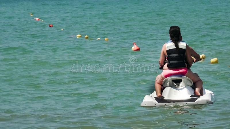Couple on waverunner jetski ride. View from behind stock image