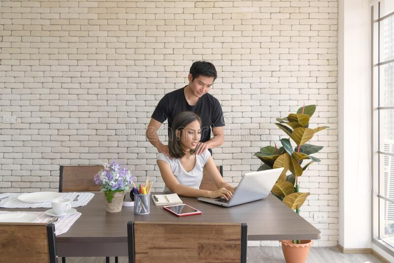 Couple wear casual clothing relaxing while sitting at big wooden table in modern kitchen and working with computer laptop at home. royalty free stock photography