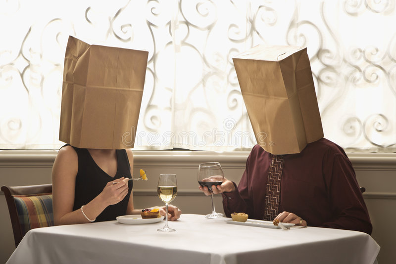 Couple wearing bags. Mid adult Caucasian couple dining in a restaurant with paper bags over heads royalty free stock images