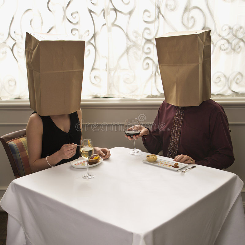 Couple wearing bags. Mid adult Caucasian couple dining in a restaurant with paper bags over heads stock photo