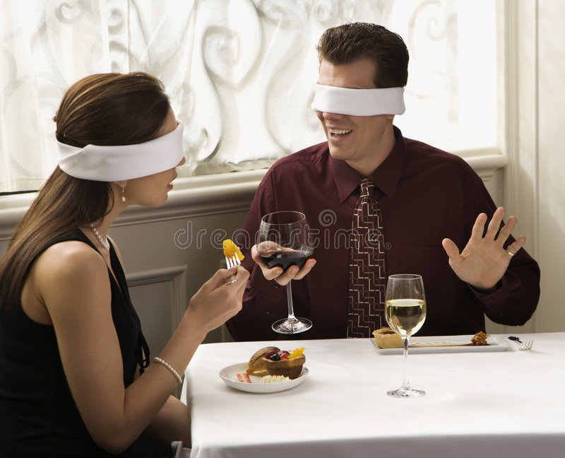 Couple wearing blindfolds. Mid adult Caucasian couple dining in a restaurant with blindfolds over eyes royalty free stock photos