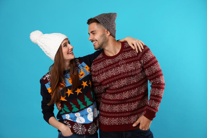 Couple wearing Christmas sweaters and hats. On blue background royalty free stock image