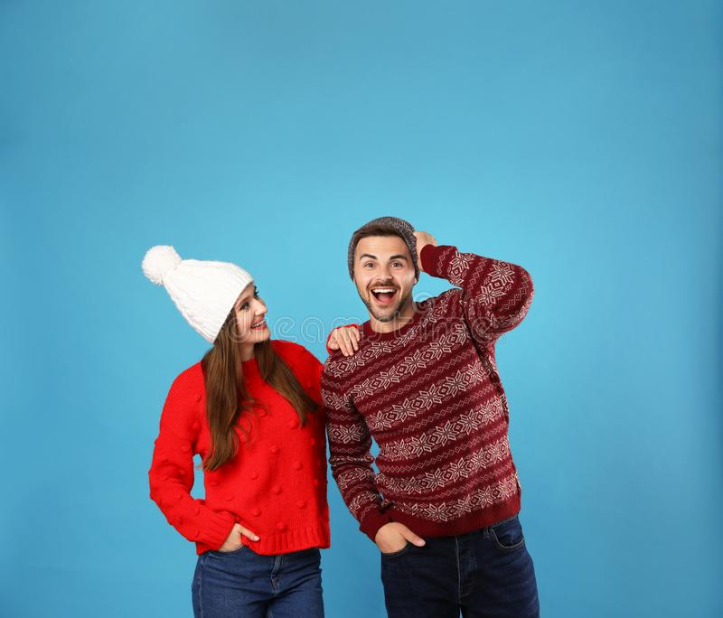 Couple wearing Christmas sweaters and hats on blue. Background royalty free stock images