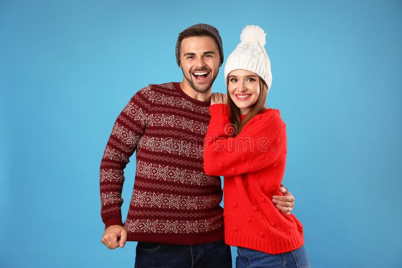Couple wearing Christmas sweaters and hats on blue. Background stock images