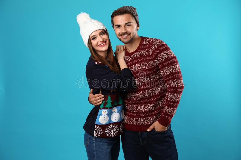 Couple wearing Christmas sweaters and hats. On blue background royalty free stock photos
