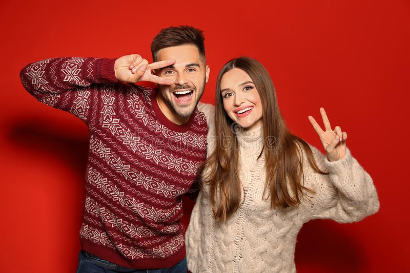Couple wearing Christmas sweaters on background royalty free stock images