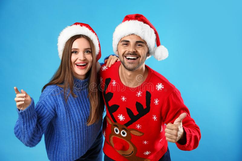 Couple wearing Christmas sweaters and Santa hats. On blue background stock photos