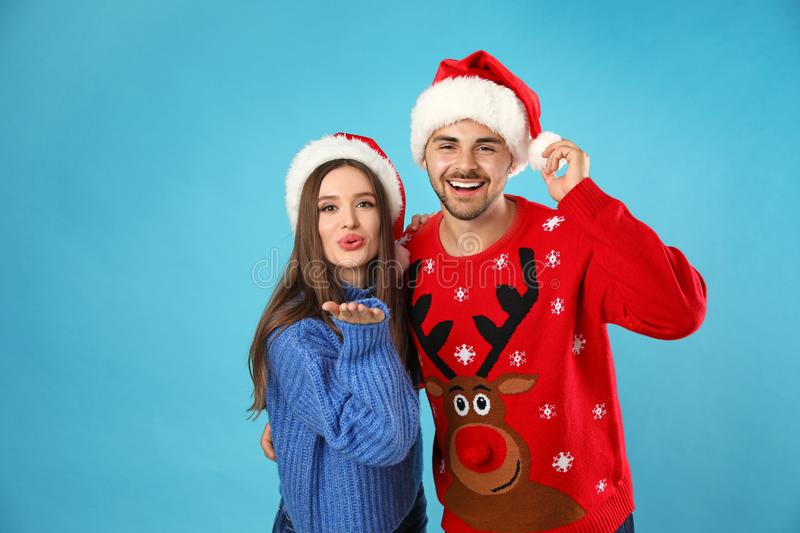 Couple wearing Christmas sweaters and Santa hats on background. Couple wearing Christmas sweaters and Santa hats on blue background stock photos