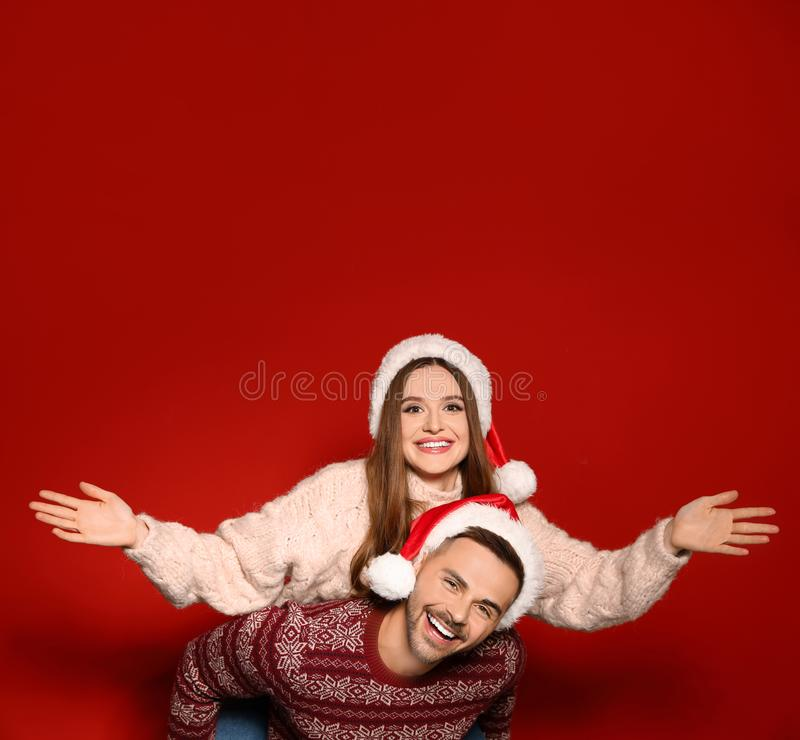 Couple wearing Christmas sweaters and Santa hats. On red background stock images