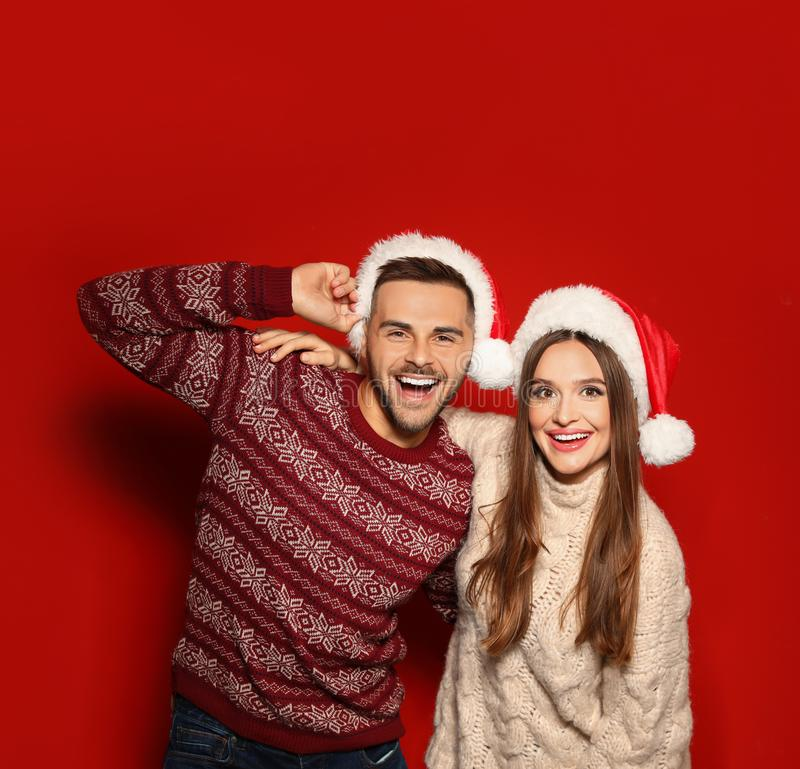 Couple wearing Christmas sweaters and Santa hats. On red background stock photography