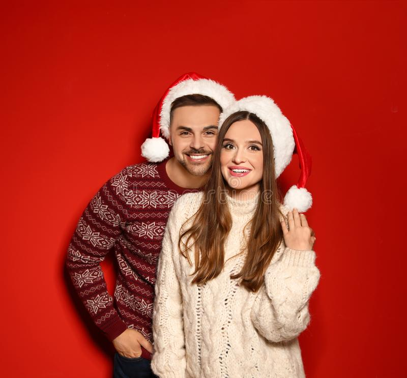 Couple wearing Christmas  and Santa hats on red background. Couple wearing Christmas sweaters and Santa hats on red background royalty free stock photos