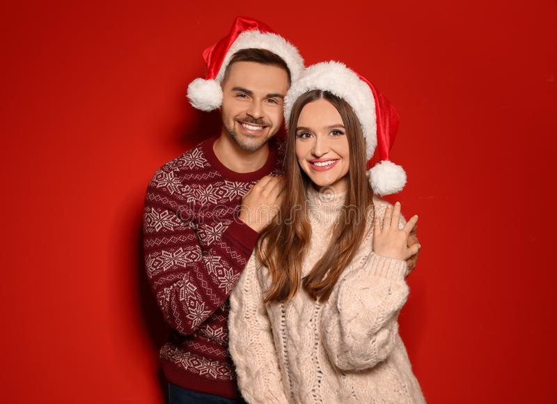 Couple wearing Christmas sweaters and Santa hats on red. Background royalty free stock photography