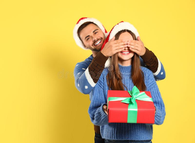 Couple wearing Christmas sweaters and Santa hats. On yellow background royalty free stock photography