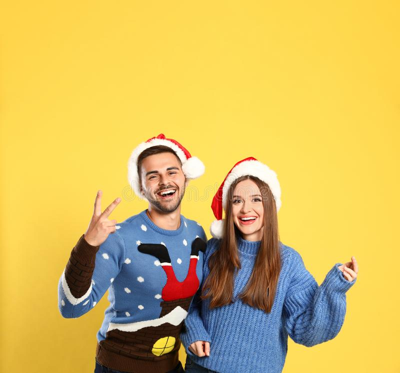 Couple wearing Christmas sweaters and Santa hats. On yellow background stock photos