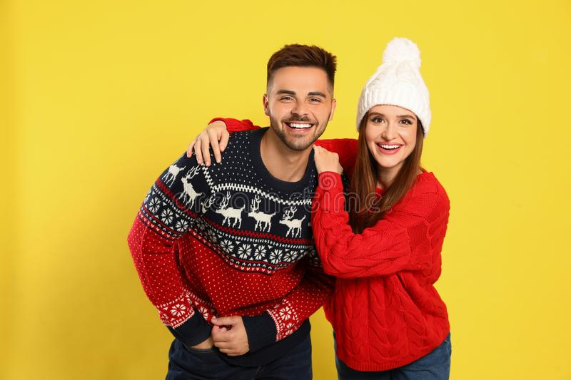 Couple wearing Christmas sweaters on yellow royalty free stock photography