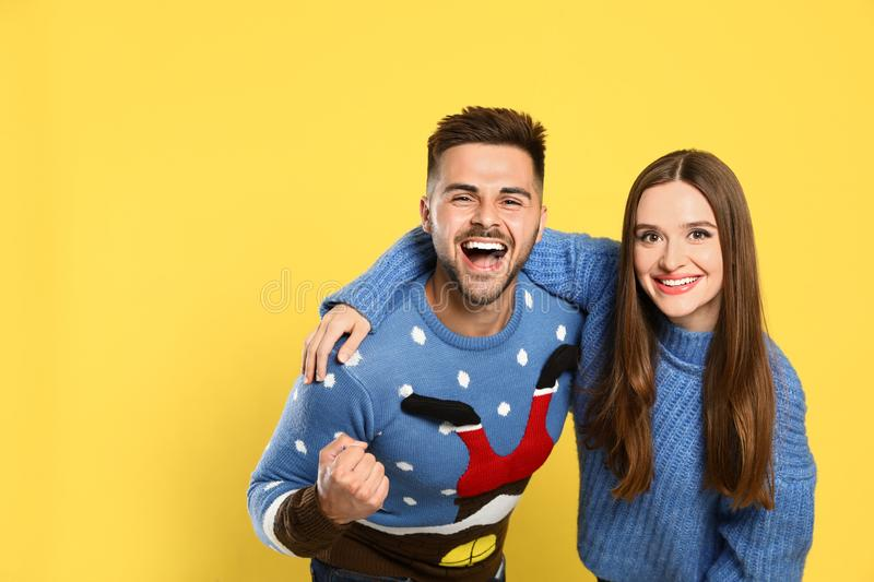 Couple wearing Christmas sweaters on background royalty free stock photo