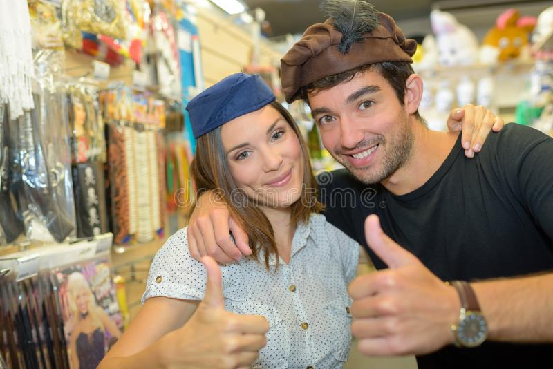 Couple wearing funny hats in costume shop royalty free stock image