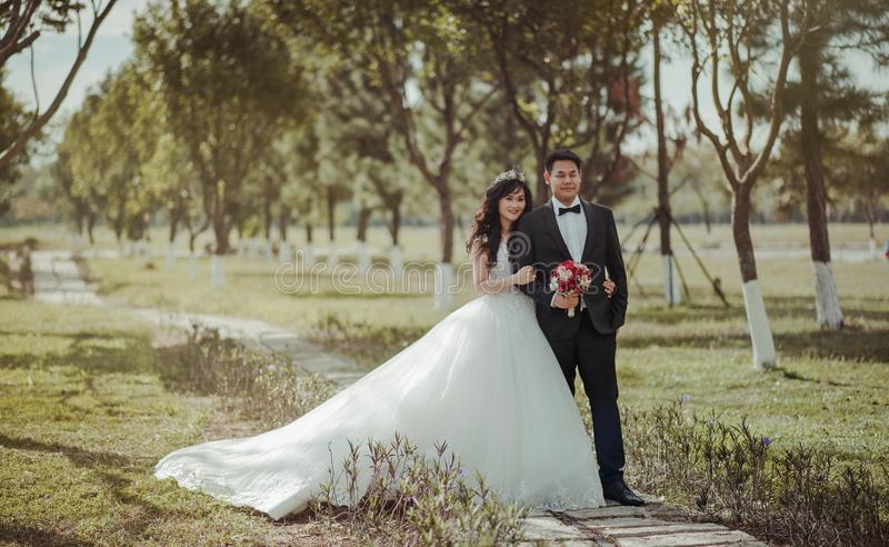 Couple Wearing Gown and Suit Jacket Standing and Pose for Picture stock photos
